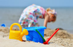 Little girl playing on the sand beach Stock Images
