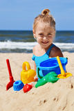 Little girl playing on the sand beach Stock Image