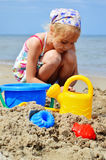 Little girl playing on the sand beach Stock Photography