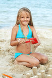 Little girl playing with sand on the beach Stock Image