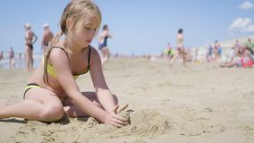 Little girl playing with sand on beach. Enjoying a lovely vacation. stock video