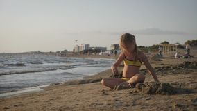 Little girl playing with sand on beach. Enjoying a lovely vacation. stock video footage