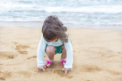 Little girl playing with the sand on the beach Royalty Free Stock Images
