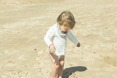 Little girl playing with the sand on the beach stock photos