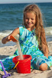 Little girl playing with sand on the beach Royalty Free Stock Photos