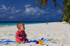 Little girl playing on sand beach Stock Photography