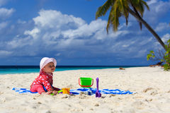 Little girl playing on sand beach Stock Photos