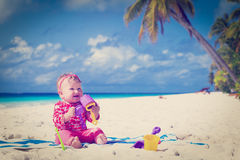 Little girl playing on sand beach Stock Image
