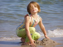 Little girl playing in the sand Berwick Northumberland Stock Photos