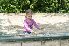 Little girl playing in the sand box. Stock Images