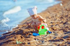 Little girl playing in sand. Cute little girl sitting on the beach and playing with plastic toys royalty free stock images