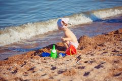 Little girl playing in sand. Cute little girl sitting on the beach and playing with plastic toys royalty free stock photography