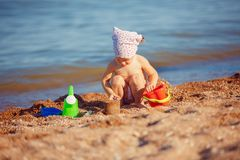 Little girl playing in sand. Cute little girl sitting on the beach and playing with plastic toys stock image