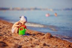 Little girl playing in sand. Cute little girl sitting on the beach and playing with plastic toys stock photo