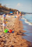 Little girl playing in sand. Cute little girl sitting on the beach and playing with plastic toys royalty free stock photo