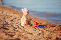Little girl playing in sand. Cute little girl sitting on the beach and playing with plastic toys royalty free stock image