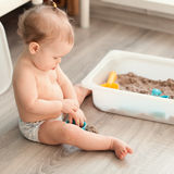 Little girl playing with sand on floor Royalty Free Stock Photo
