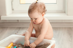 Little girl playing with sand on floor Royalty Free Stock Image