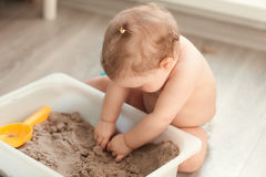 Little girl playing with sand on floor Stock Photos
