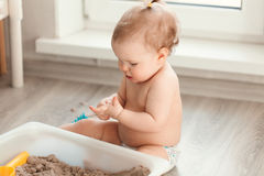 Little girl playing with sand on floor Royalty Free Stock Photography