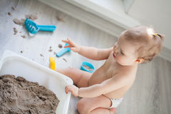 Little girl playing with sand on floor Stock Images