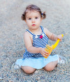 Little girl playing in the sand with a rake. Portrait of little girl playing in the sand with a rake Stock Photo