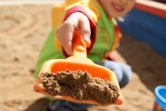 Little girl playing with sand. In the summer Stock Image