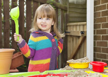 Girl playing with sand. Little girl wearing bright striped cardigan holding a green shovel playing with sand and colorful plastic bowls Stock Photography