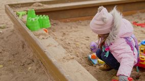 Little girl playing in a sandbox.  stock video