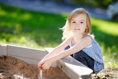 Little girl playing in a sandbox Stock Photos