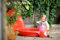 Little girl playing in a sandbox Stock Photo
