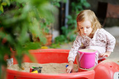 Little girl playing in a sandbox. Adorable little girl playing in a sandbox Stock Photography