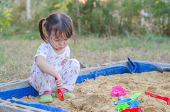 Little girl playing in sandbox Stock Image