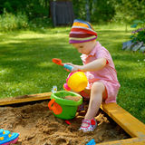 Little girl playing in the sandbox royalty free stock image