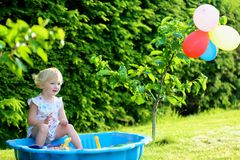 Little girl playing with sandbox in the garden. Happy little child, adorable blonde toddler girl having fun playing outdoors in party decorated garden with Stock Photo