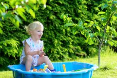 Little girl playing with sandbox in the garden. Happy little child, adorable blonde toddler girl having fun playing outdoors in party decorated garden with Stock Image