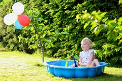 Little girl playing with sandbox in the garden. Happy little child, adorable blonde toddler girl having fun playing outdoors in party decorated garden with Royalty Free Stock Photo