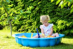 Little girl playing with sandbox in the garden. Happy little child, adorable blonde toddler girl having fun playing outdoors in party decorated garden with Royalty Free Stock Photos