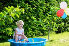 Little girl playing with sandbox in the garden. Happy little child, adorable blonde toddler girl having fun playing outdoors in party decorated garden with Stock Images