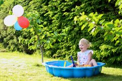 Little girl playing with sandbox in the garden. Happy little child, adorable blonde toddler girl having fun playing outdoors in party decorated garden with Royalty Free Stock Photography