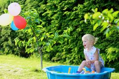 Little girl playing with sandbox in the garden. Happy little child, adorable blonde toddler girl having fun playing outdoors in party decorated garden with Royalty Free Stock Images