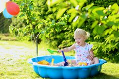 Little girl playing with sandbox in the garden Stock Image
