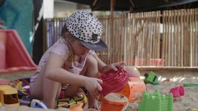 Little Girl Playing In Sandbox with sand and toys. In 4K stock footage