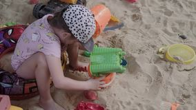 Little Girl Playing In Sandbox with sand and toys. In 4K stock video