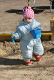 The little girl playing in a sandbox. A scoop and a bucket Stock Image