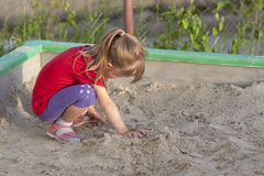Little girl playing in sandbox on a sunny summer day. Little girl playing in sandbox on  sunny summer day Stock Photography