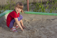 Little girl playing in sandbox on a sunny summer day. Little girl playing in sandbox on  sunny summer day Stock Photo