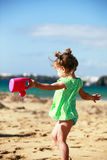 Little girl playing on sandy beach Stock Images