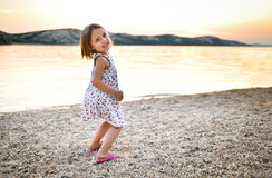Little girl is playing on sandy beach in sunset or sunrise. Royalty Free Stock Photography