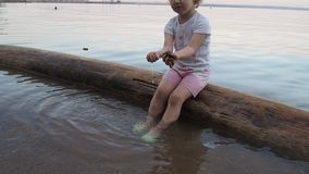 A little girl playing on the sea with pebbles in her hands. She sits on a log and washes stones. In the evening, close stock footage